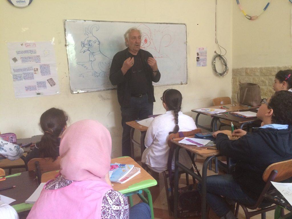Denis Martinez explique à des enfants scolarisés l'importance du trait dans l'écriture.